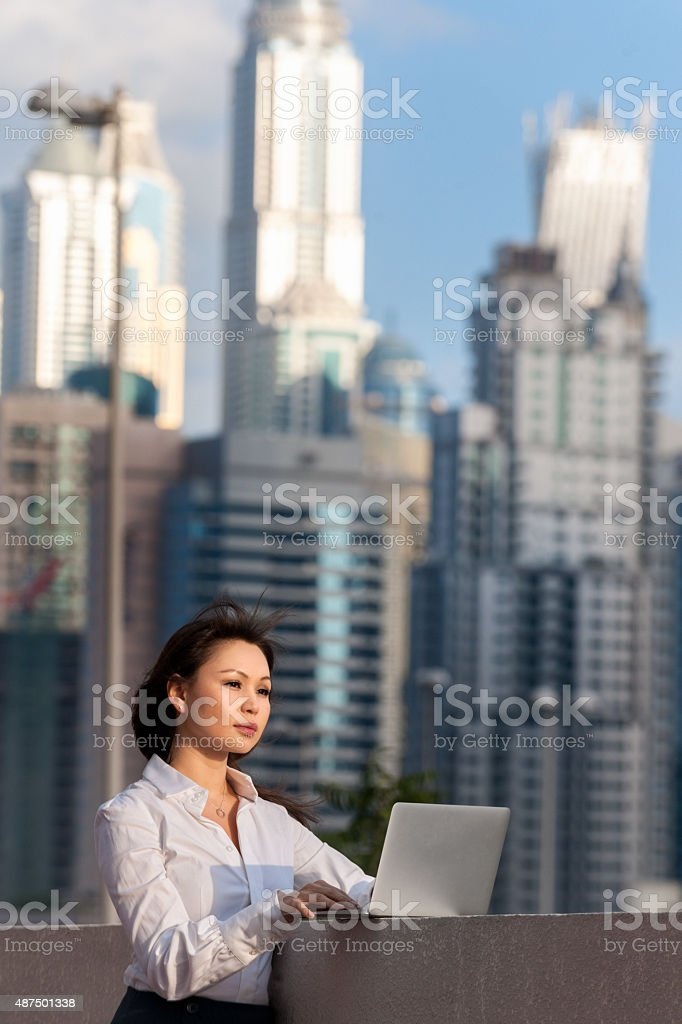 businesswoman in the last sun using laptop in Dubai stock photo