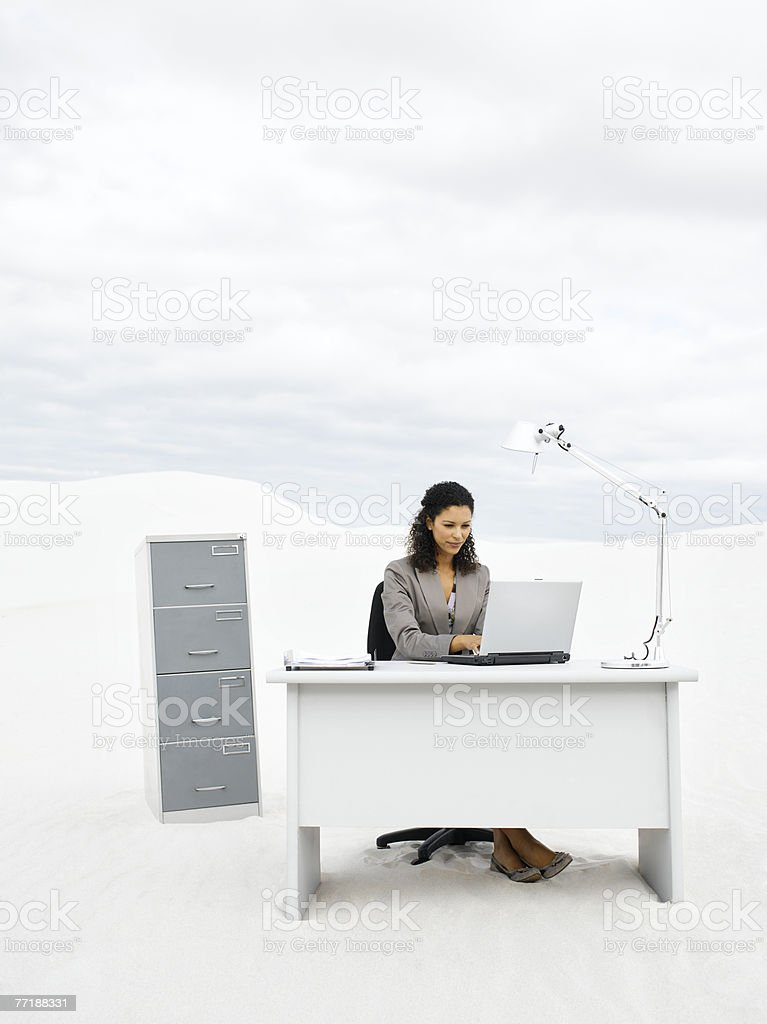 A businesswoman in the middle of nowhere at her desk royalty-free stock photo