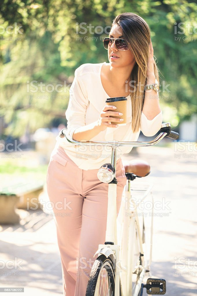 Businesswoman in the park on bike and having a coffee stock photo