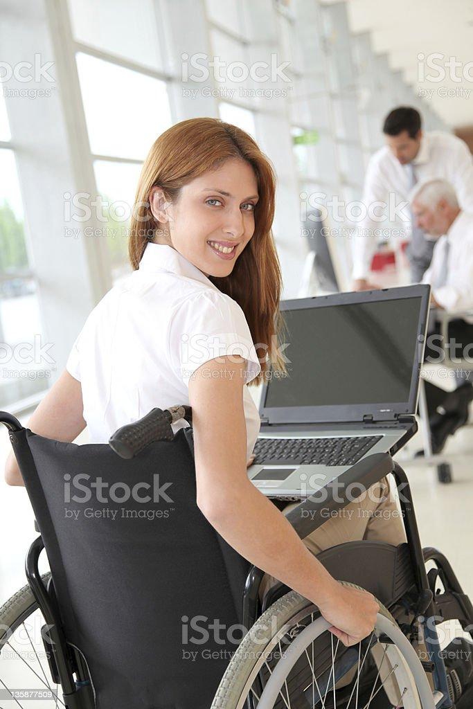 Businesswoman in wheelchair at work stock photo