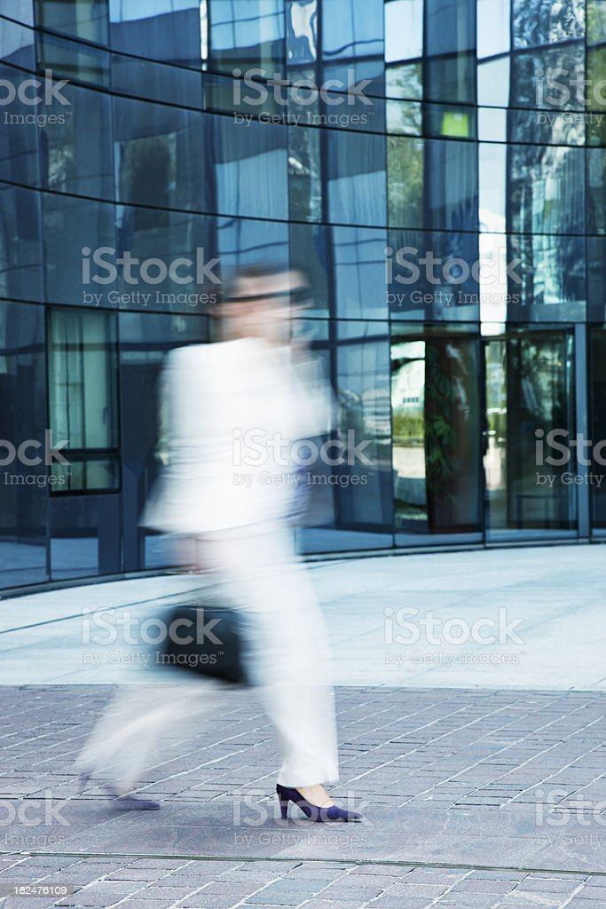Businesswoman in White Suit Walking Along Office Building, Blurred Motion royalty-free stock photo