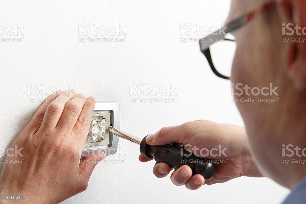 Businesswoman installing a light switch stock photo