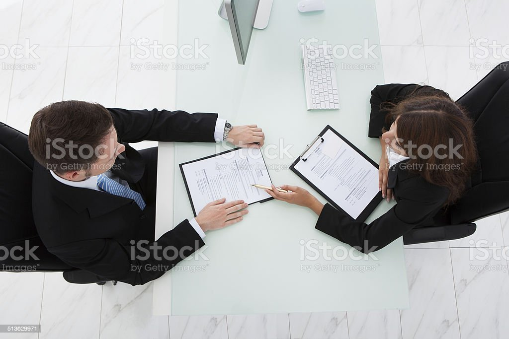 Businesswoman Interviewing Male Candidate In Office stock photo