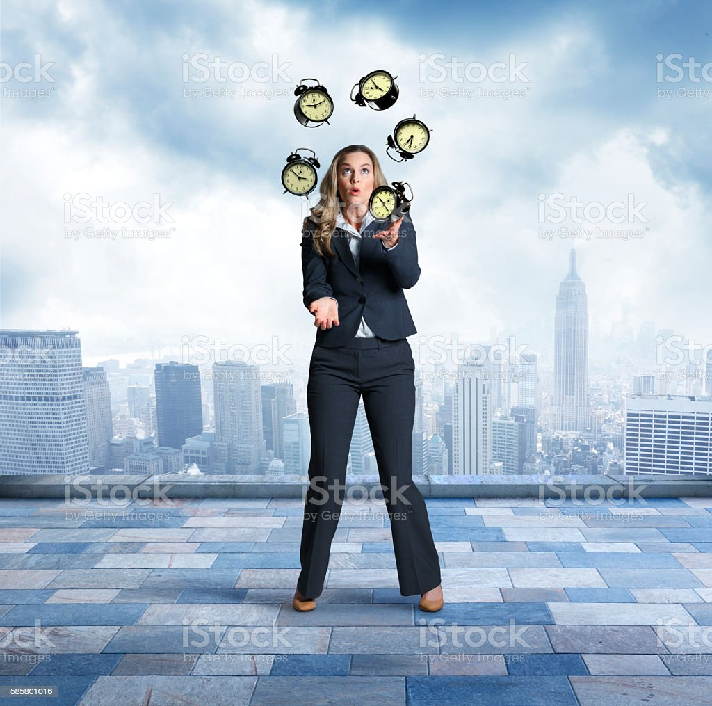 Businesswoman Juggling Alarm Clocks In Front Of City Skyline stock photo