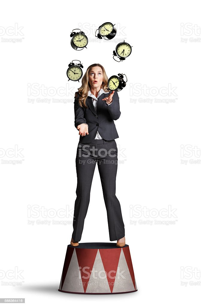 Businesswoman Juggling Alarm Clocks On White Background stock photo
