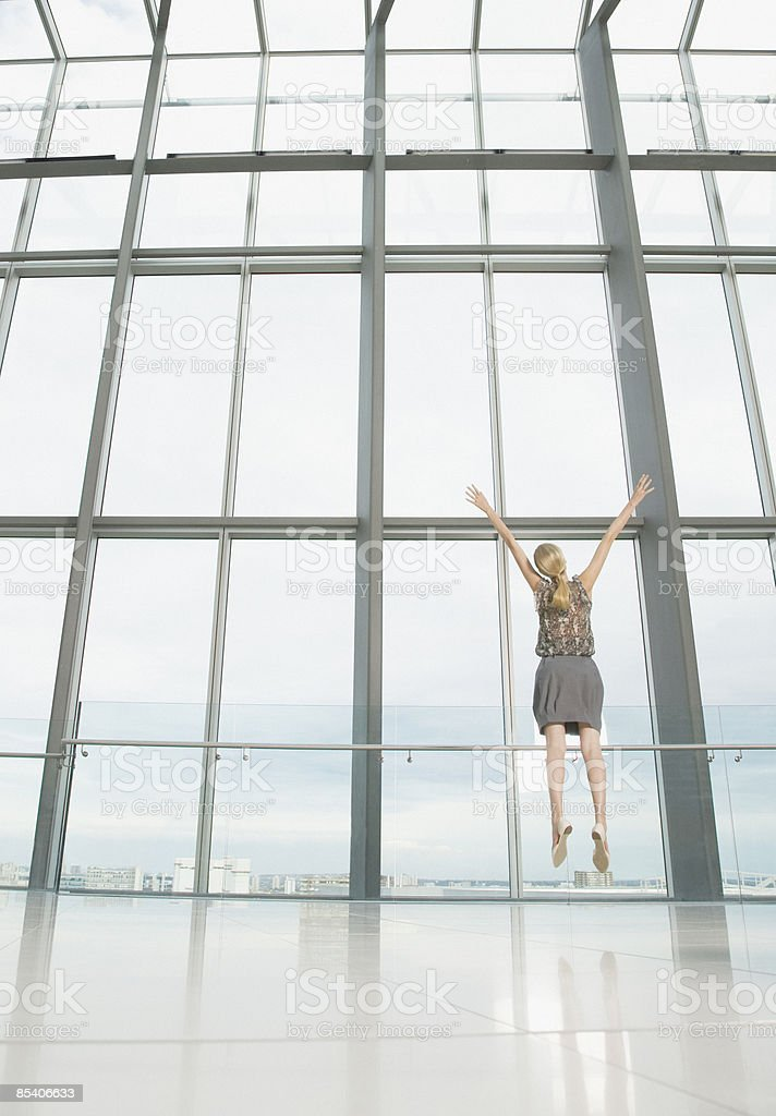 Businesswoman jumping in modern lobby royalty-free stock photo