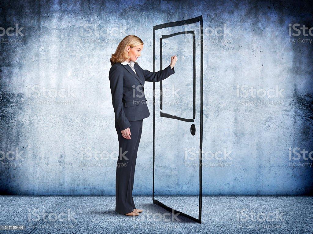 Businesswoman Knocking At Make Believe Door stock photo