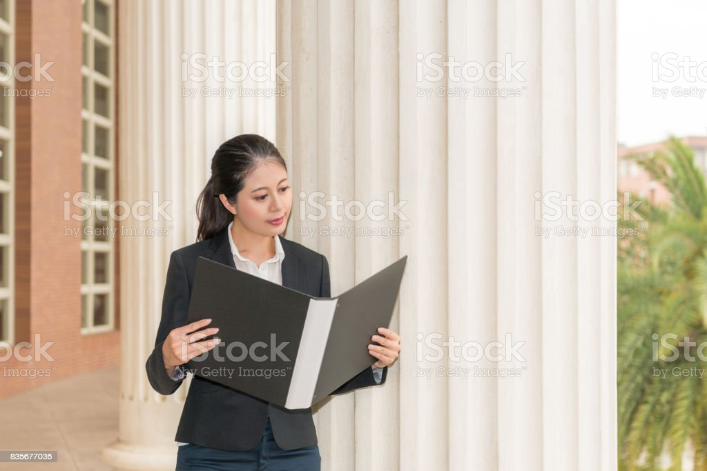 businesswoman lawyer holding folder and reading stock photo