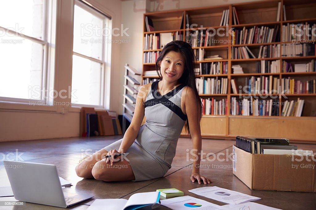 Businesswoman Laying Documents On Floor To Plan Project stock photo