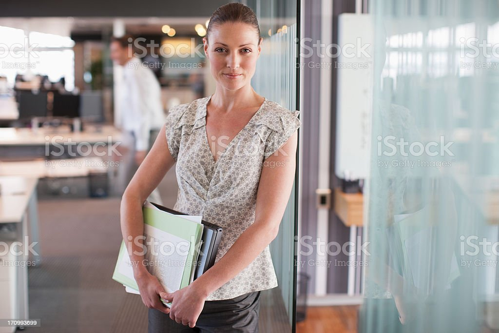 Businesswoman leaning against office wall royalty-free stock photo