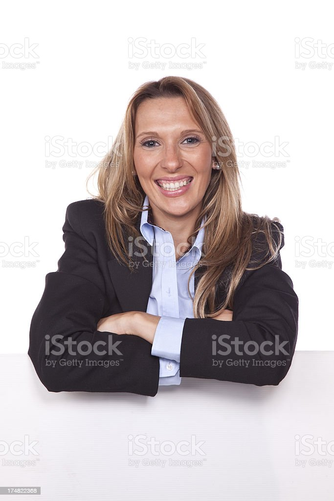 Businesswoman leaning on a billboard royalty-free stock photo