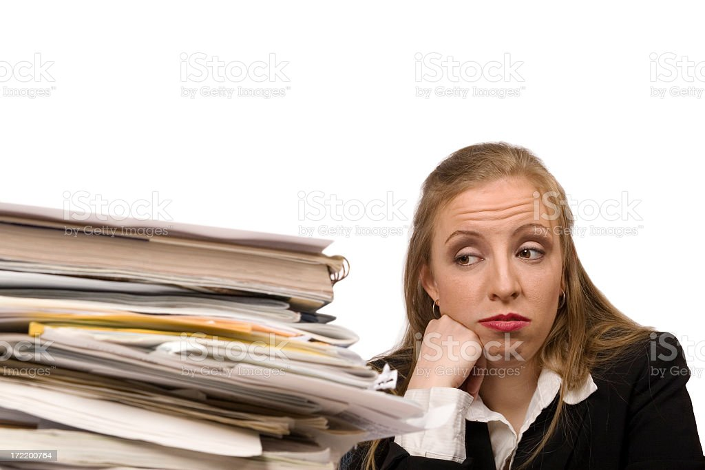 Businesswoman looking a stack of files and papers tiredly stock photo