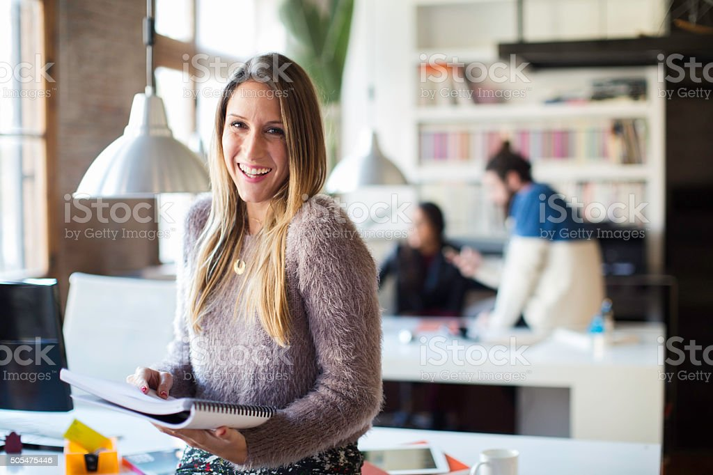 Businesswoman looking and smiling at camera in small office. stock photo