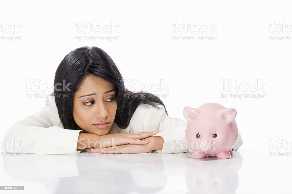 Businesswoman looking at a piggy bank stock photo