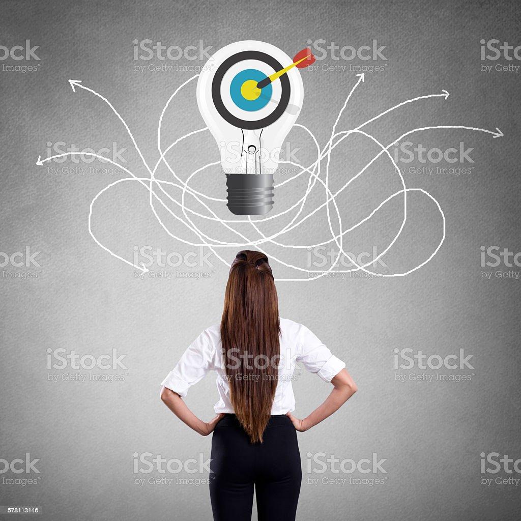 Businesswoman looking at bull's eye on light bulb stock photo