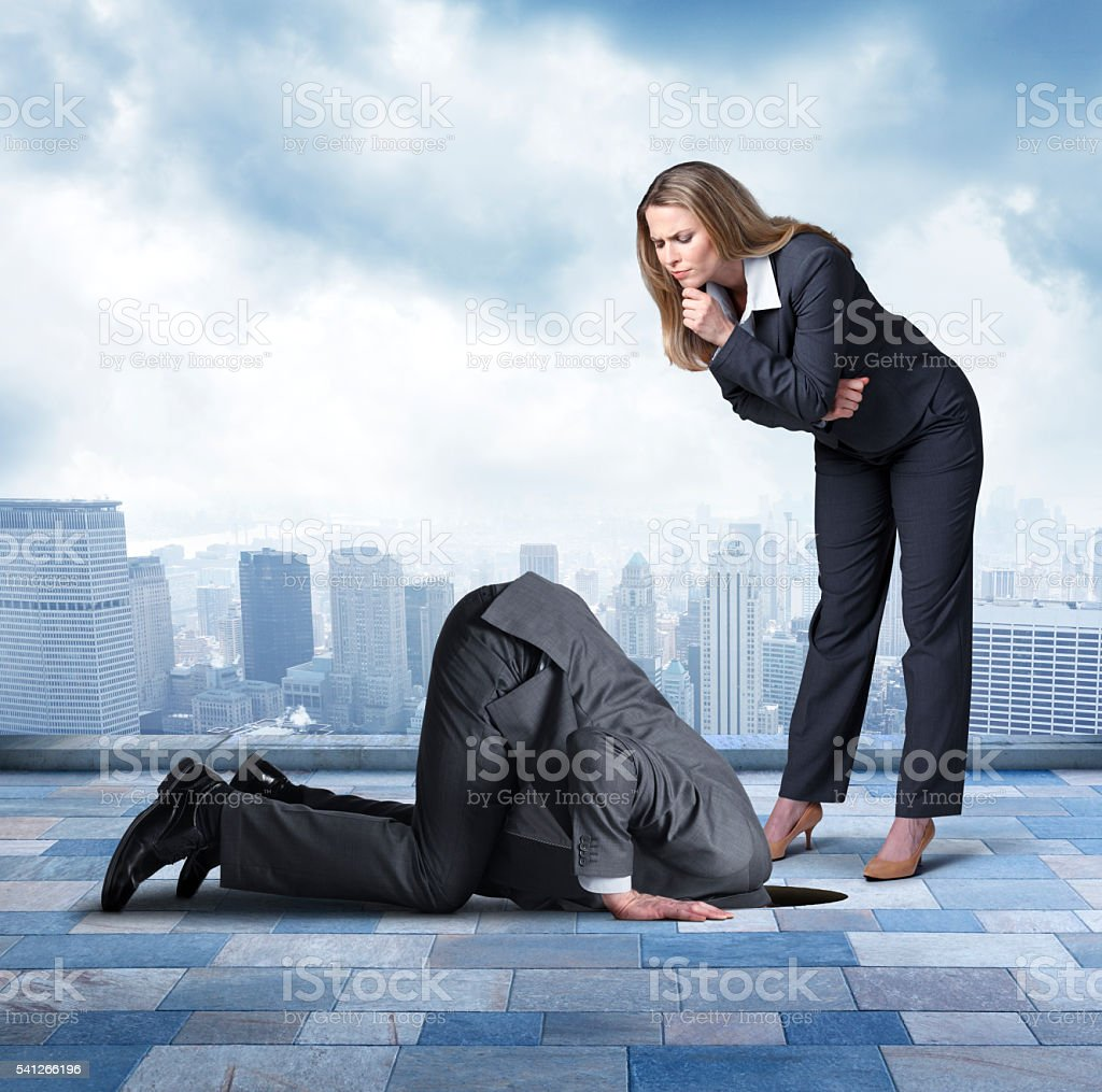 Businesswoman Looking At Businessman Who Has Head Buried In Hole stock photo