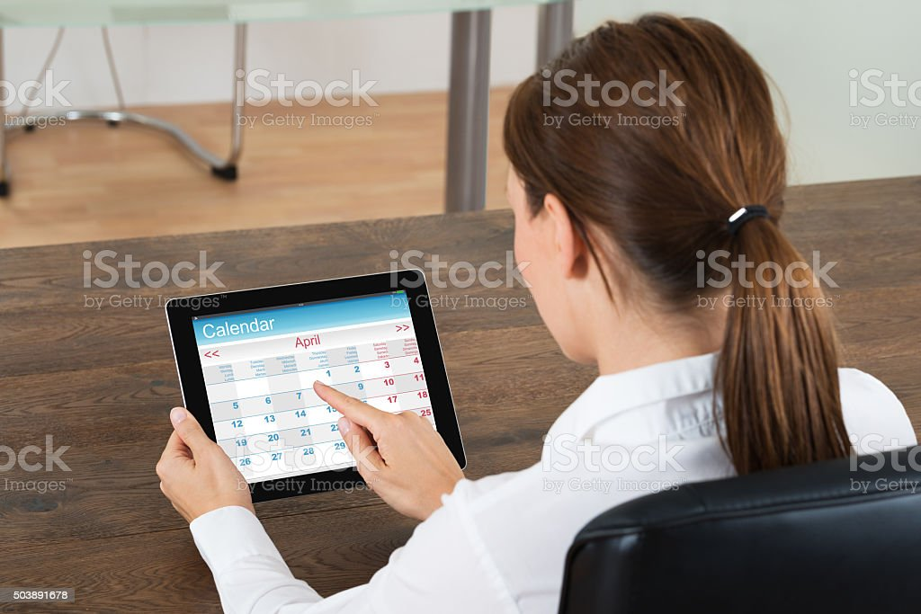 Businesswoman Looking At Calendar On Digital Tablet stock photo