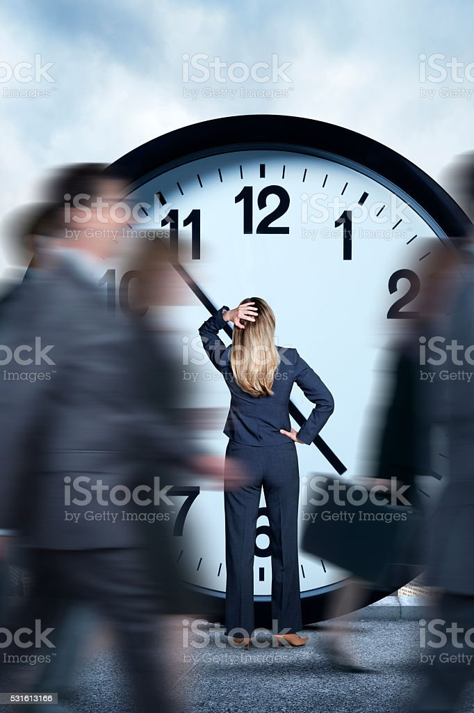 Businesswoman Looking At Clock As Others Pass Her By stock photo