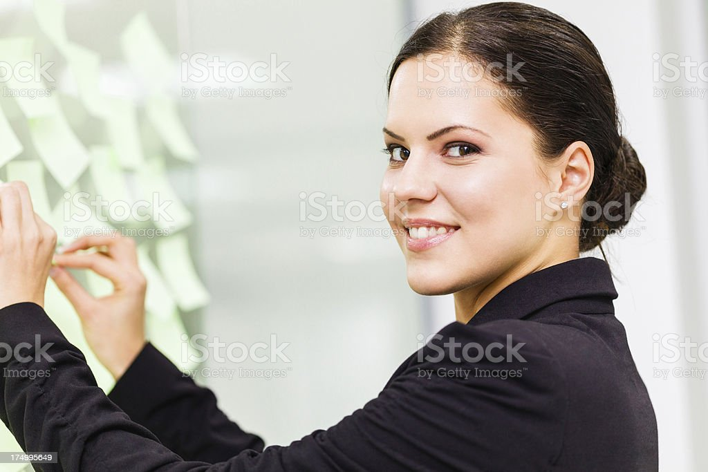 Businesswoman looking at sticky notes royalty-free stock photo