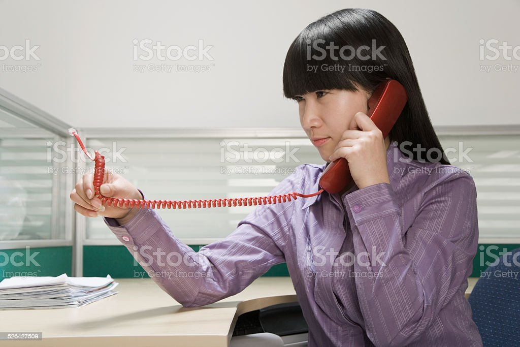 Businesswoman looking at unplugged cord of telephone receiver stock photo