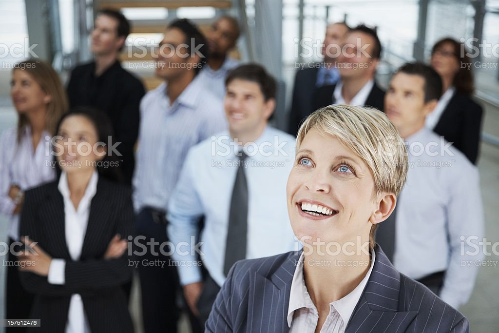Businesswoman looking away with colleagues in the background royalty-free stock photo