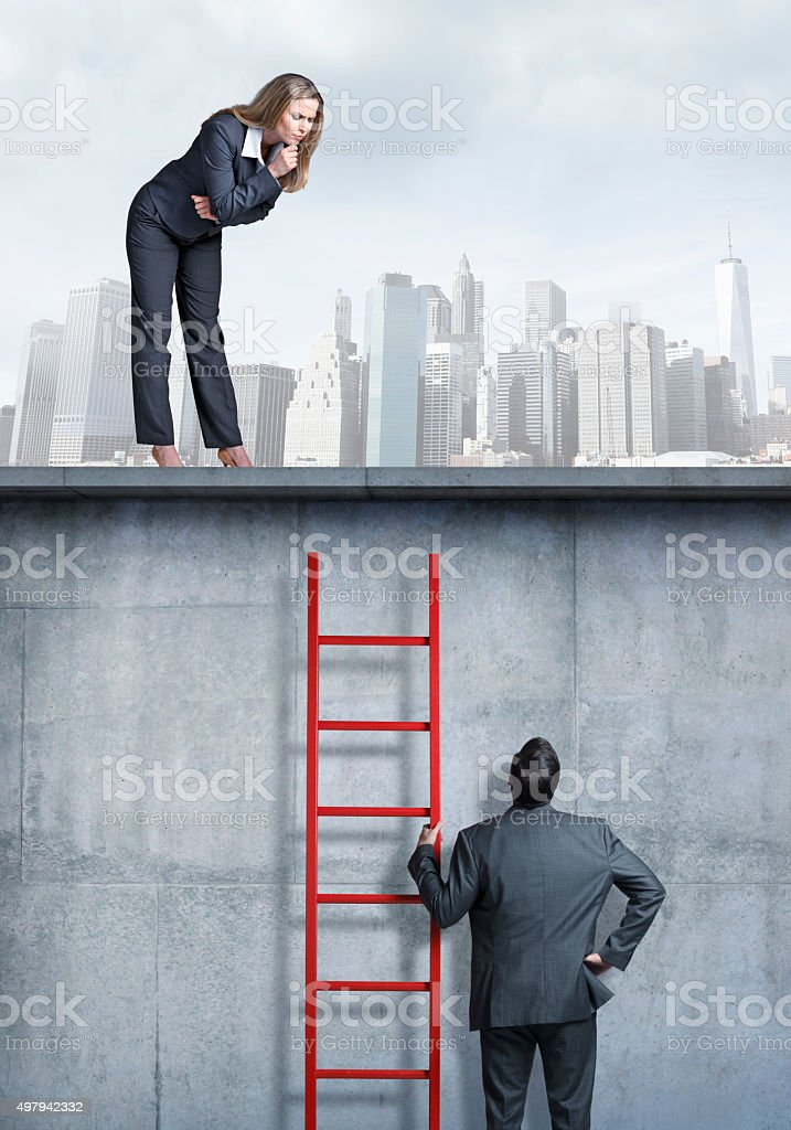 Businesswoman Looking Down At Businessman Holding A Ladder stock photo