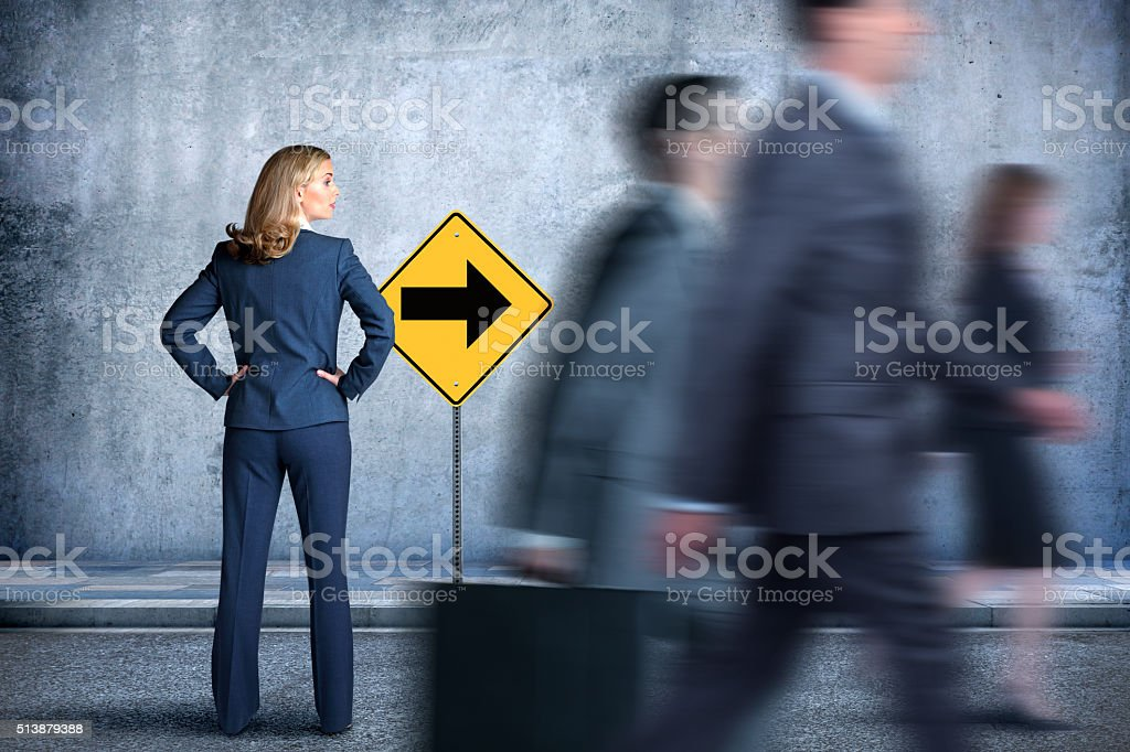 Businesswoman Looking In The Direction Everyone Is Walking stock photo