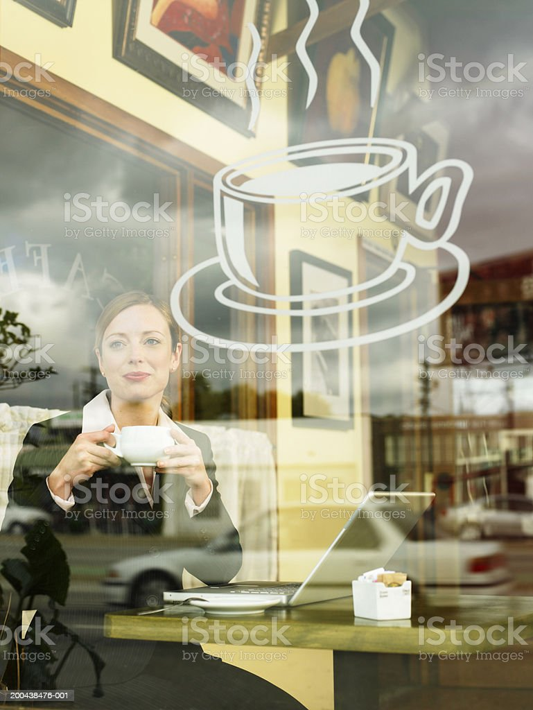 Businesswoman looking out of window in coffee shop royalty-free stock photo