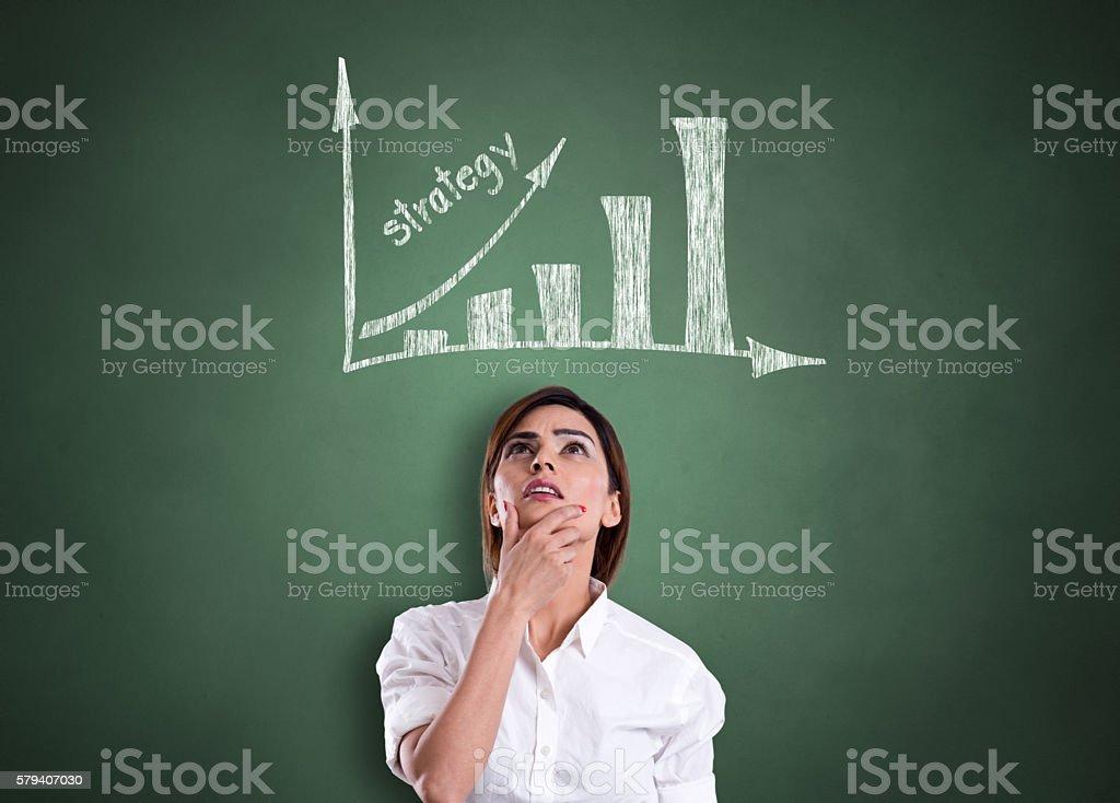 Businesswoman looking progress report on black board stock photo