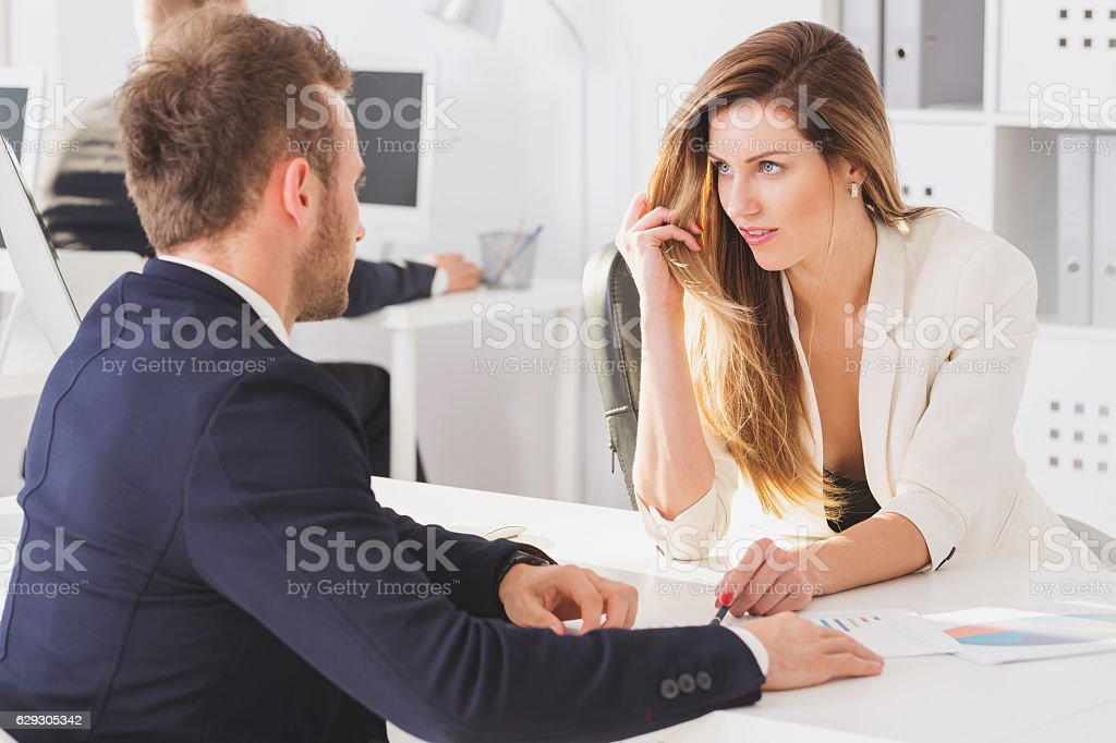 Businesswoman looking seductively at colleague stock photo