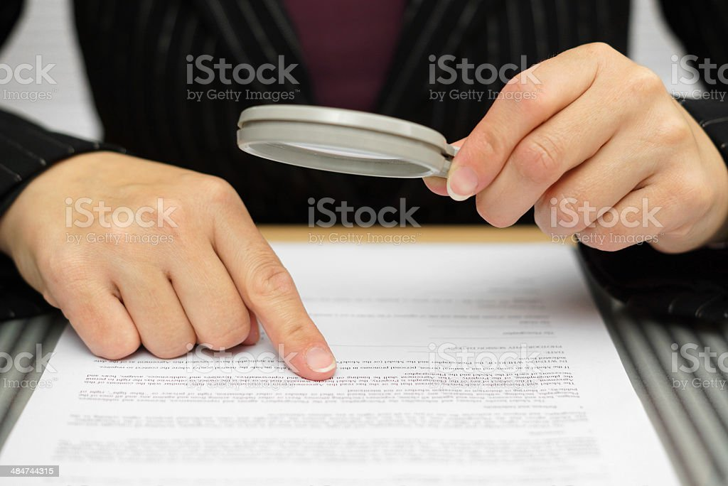 Businesswoman looking through a magnifying glass to contract stock photo