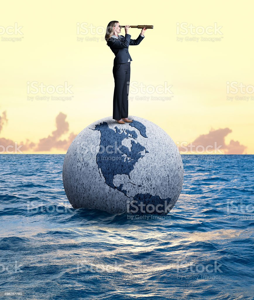 Businesswoman Looking Through Spyglass Standing On A Globe stock photo