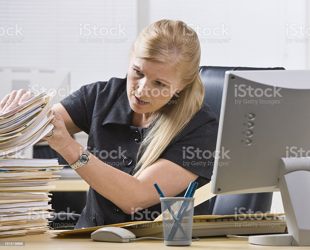 Businesswoman looking through stack of paperwork royalty-free stock photo