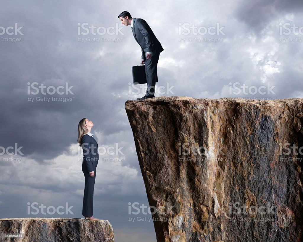 Businesswoman Looking Up At A Businessman Standing On Higher Level stock photo