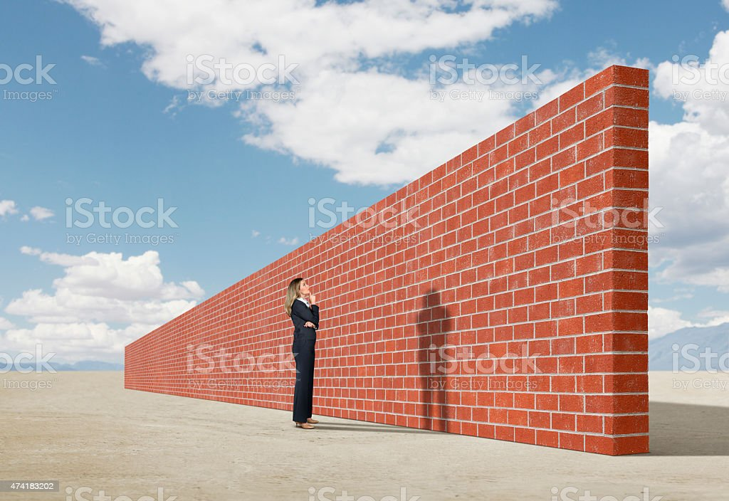 Businesswoman looking up at brick wall in middle of desert stock photo