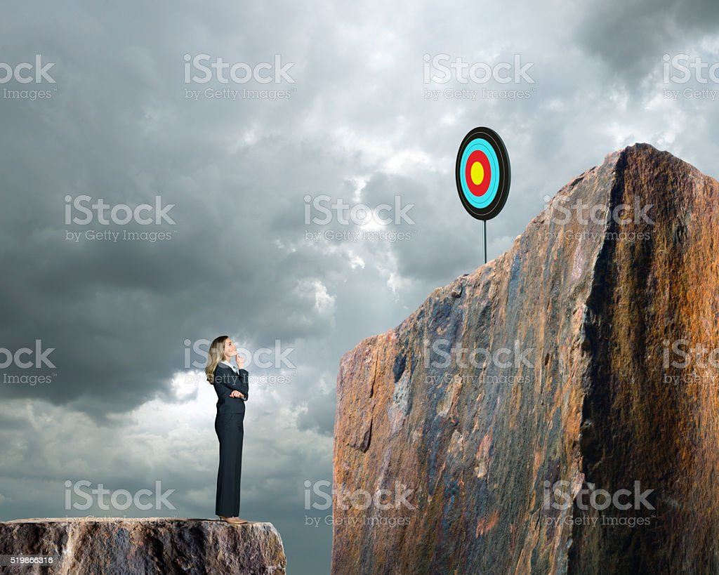 Businesswoman Looking Up At Target On Cliff Above Her stock photo