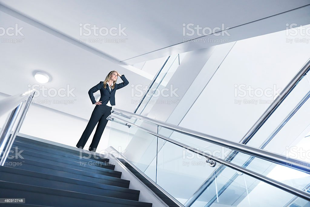 Businesswoman Looking Up To Next Flight Of Stairs stock photo