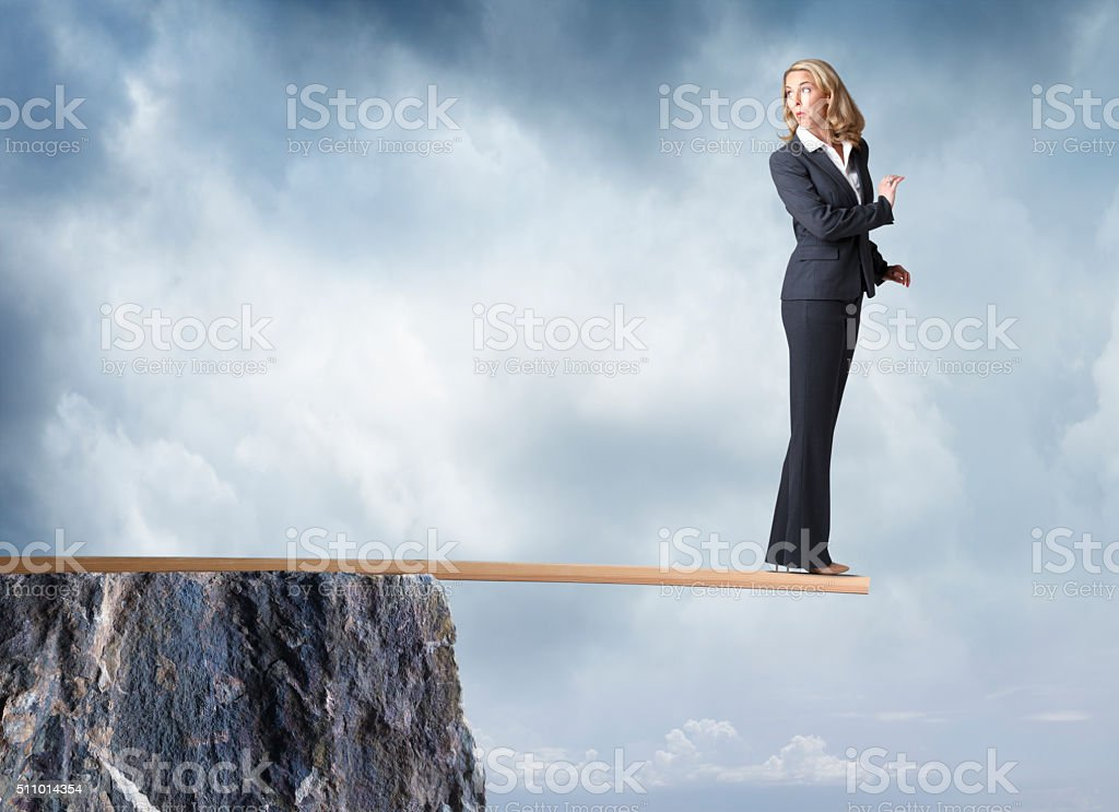 Businesswoman Looks Behind Her As She Walks Plank stock photo