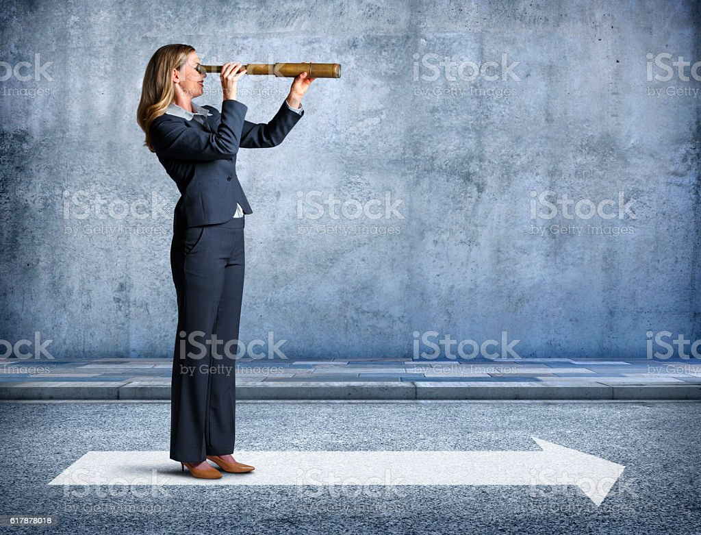 Businesswoman Looks Through Spyglasses Pointing In Direction Of Arrow stock photo