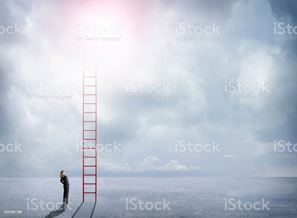 Businesswoman Looks Up At Red Ladder Extending Into The Clouds stock photo