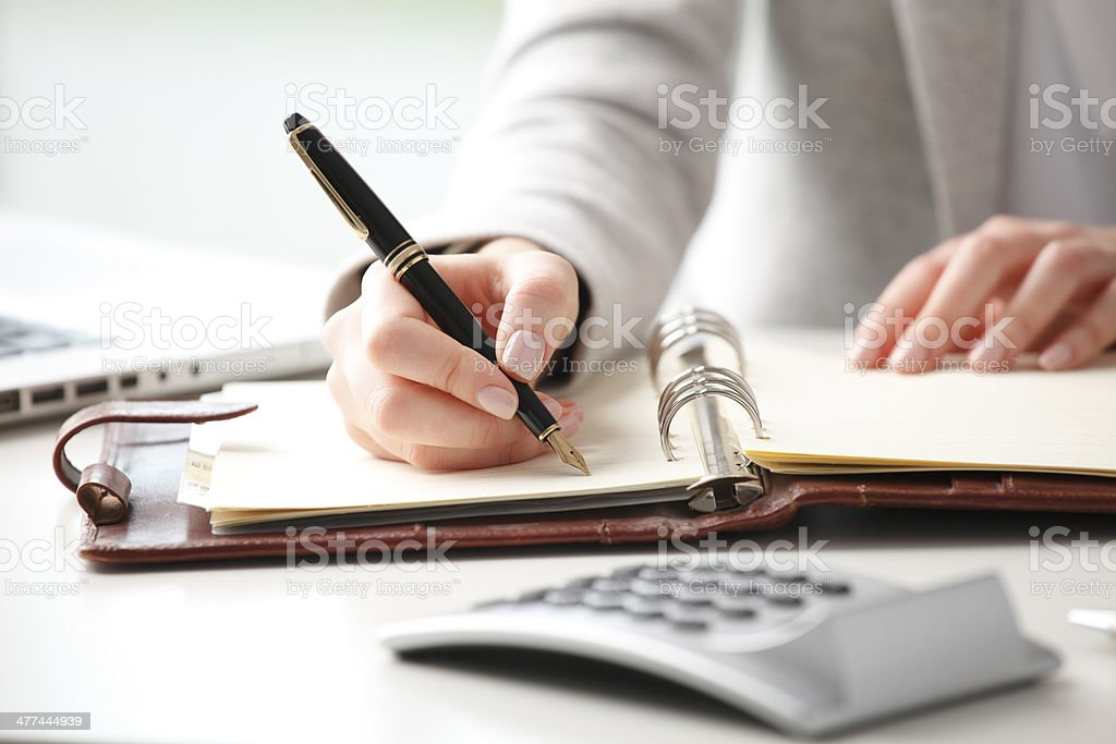Businesswoman makes a note in notebook. stock photo