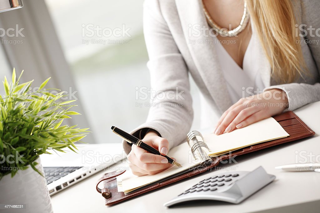 Businesswoman makes a note in notebook. royalty-free stock photo