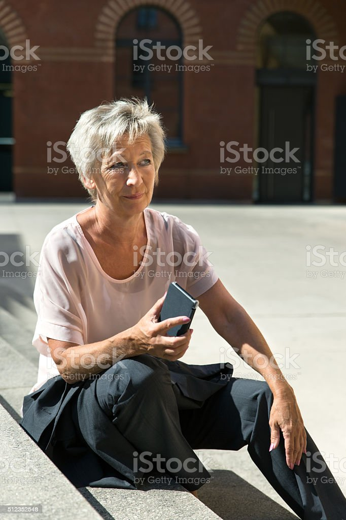 Businesswoman making a break and sitting on a stair stock photo