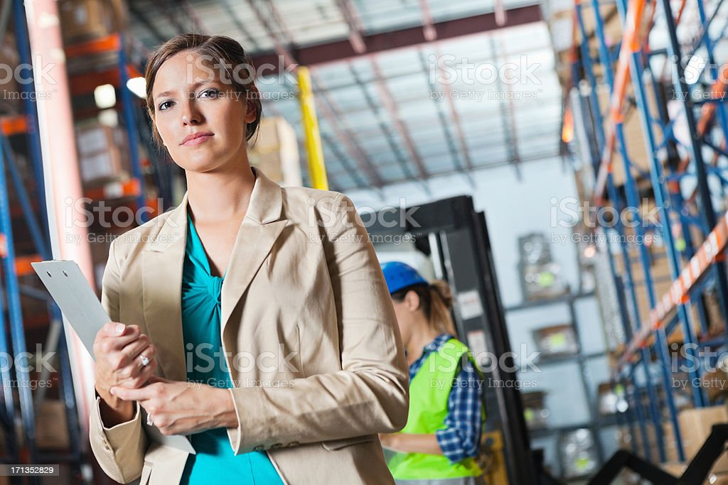 Businesswoman managing shipping warehouse royalty-free stock photo