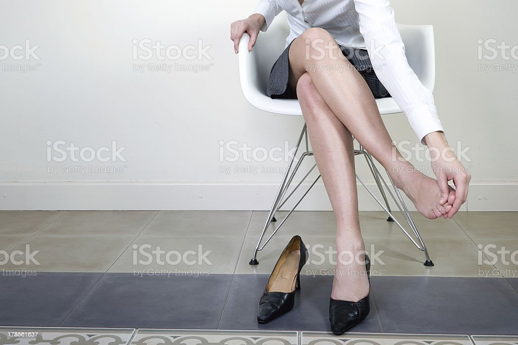 Businesswoman massaging her foot stock photo