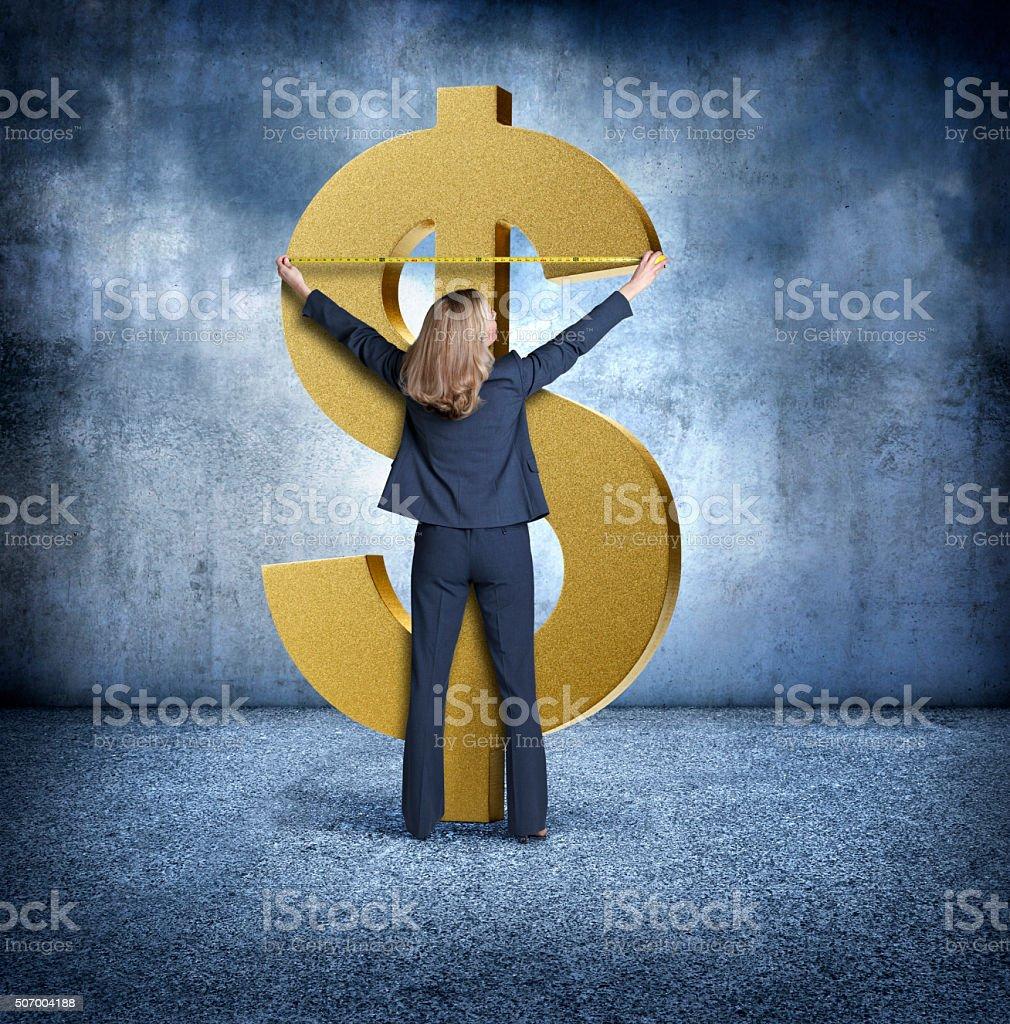 Businesswoman Measuring A Dollar Symbol stock photo