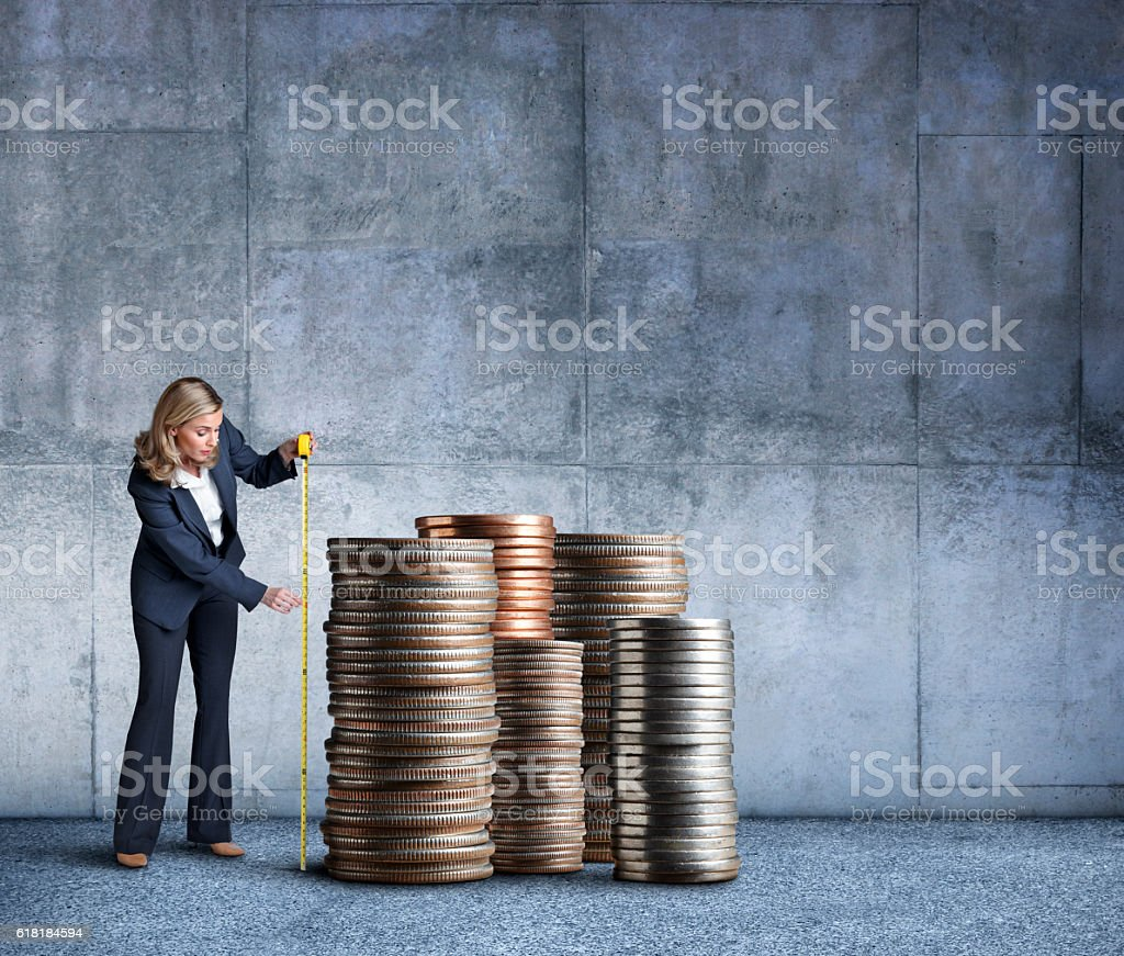 Businesswoman Measuring A Stacks Of Coins With Tape Measure stock photo