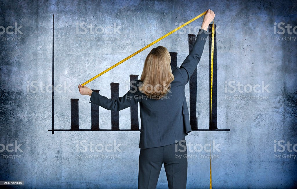 Businesswoman Measuring Growth Chart With A Tape Measure stock photo