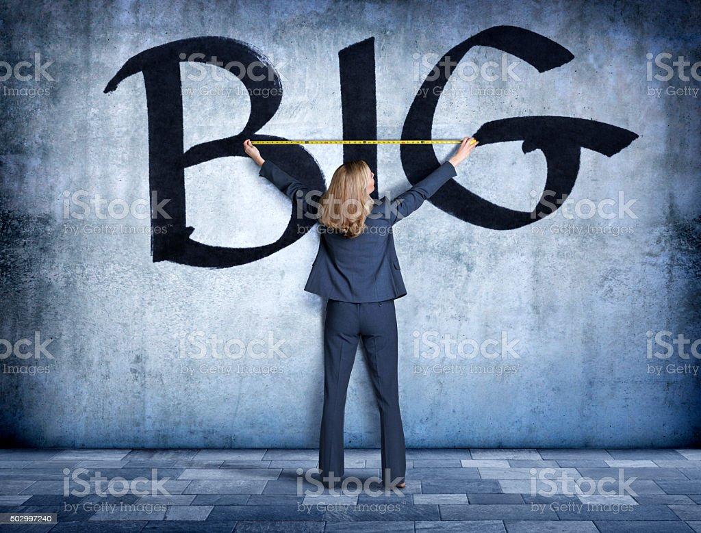 Businesswoman Measuring The Word Big stock photo
