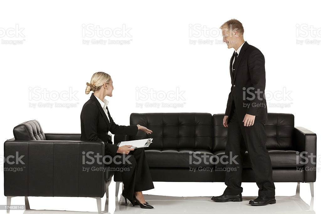 Businesswoman offering seat to a businessman royalty-free stock photo
